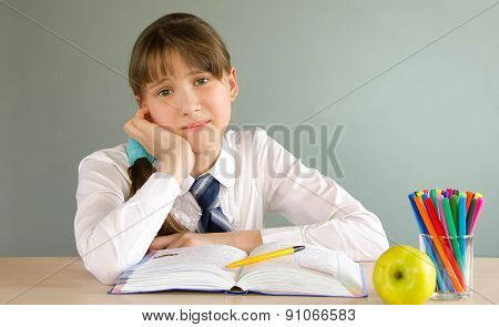 schoolgirl sitting at a desk in the classroom, smiling