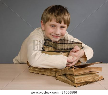 TheTeenage boy sleeping on books, smiling