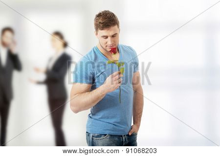 Young handsome man with red rose.