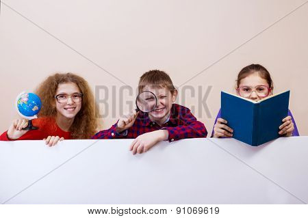 Happy smiling group of kids, friends, boys and girls, learning showing white blank placard, board.