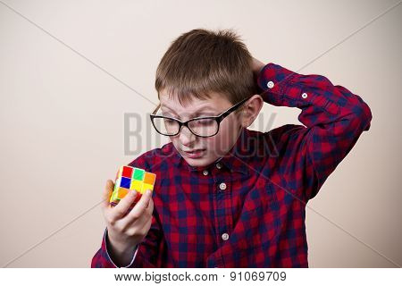 Confused little boy nerd ,holding a puzzle cube and a hand on his head