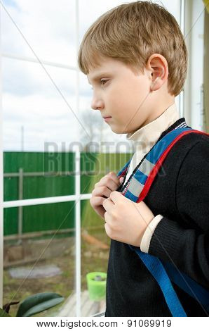 Schoolboy with a briefcase on the back of a sad looking out the window
