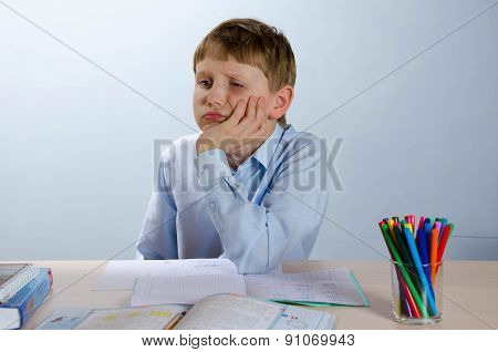 The student sitting in a classroom at a school desk, tired