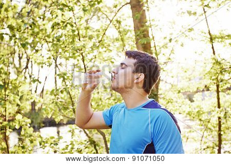Sport man drinking water bottle in a city park. Male runner athlete taking a break thirsty after run