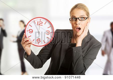Surprised businesswoman holding a big clock.