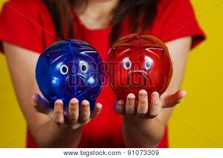 Little girl holding two piggy banks one red another blue wondering what to do.