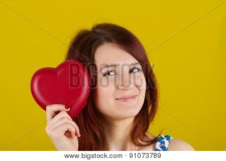 Woman showing holding  red heart. Love  concept with joyful young woman smiling isolated on yellow