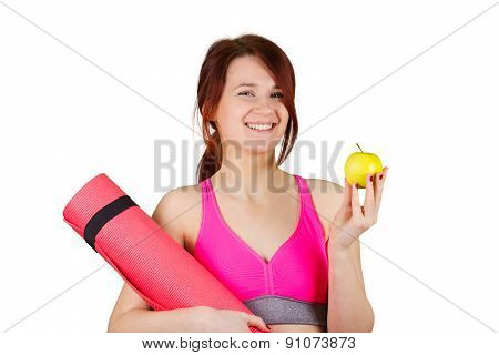 Sporty fit healthy smiling beautiful woman, red head girl holds an apple and yoga mat.Exercise, fitn