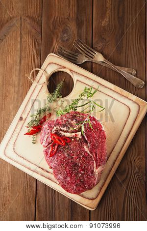 raw Beef steak on a wooden board and table