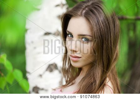 Close up, portrait of a young beautiful brunette girl on a background of leaves of a birch