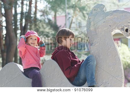 Sibling children are playing on concrete park sculpture of animal