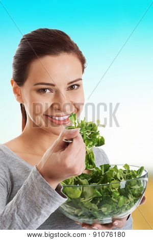 Healthy young woman eating lambs lettuce.