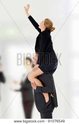 Businessman carrying woman on his shoulders.