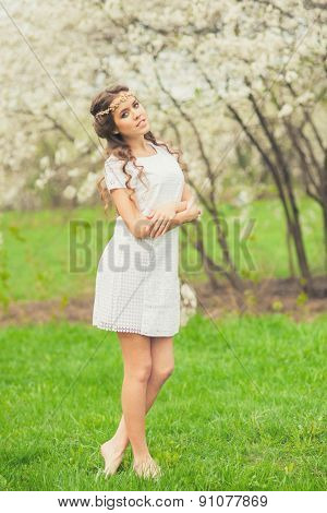 Beautiful Girl in white short dress walking in spring garden, spring time.