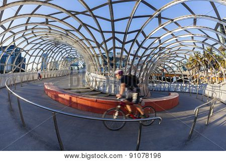 View of cyclist riding along the Webb Bridge in Docklands, Melbourne