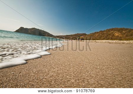 Beautiful view of foamy waves against white sand in Los Frailes beach, Ecuador