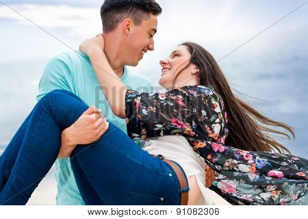 Boy Swinging Girlfriend In Arms Outdoors.