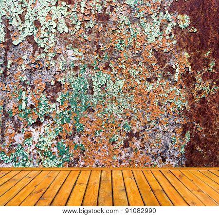 Empty grunge metal wall with wooden floor