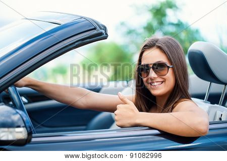 Cute Girl In Convertible Doing Thumbs Up.