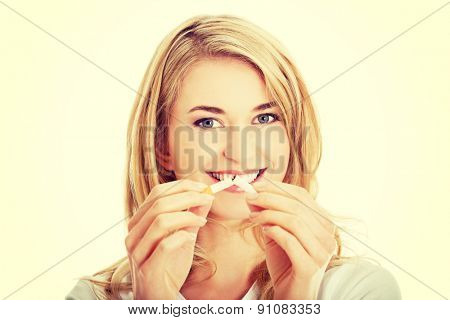 Young beautiful woman holding broken cigarette in front.