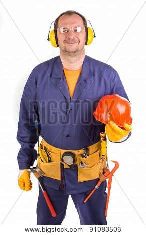 Worker in ear muffs holding hard hat.