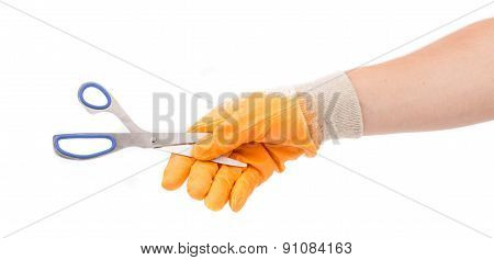 Hand in yellow glove holding scissors.