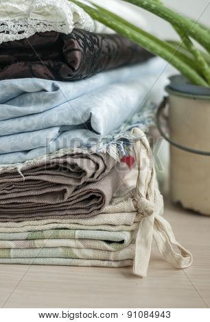 Stack of different fabrics and aloe plant.