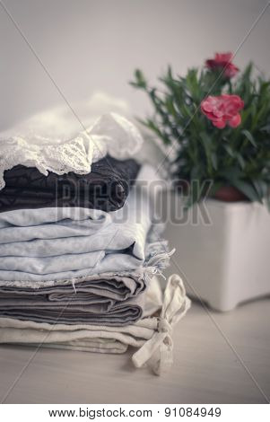 Stack of different fabrics and blooming plant in pot.