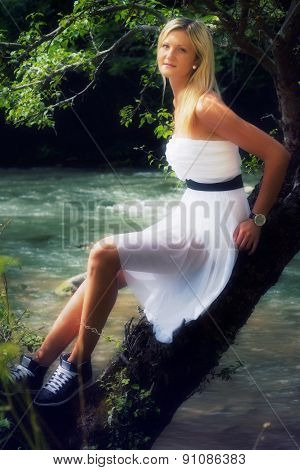 beautiful young woman in a radiant white summer dress sitting on a tree at a river