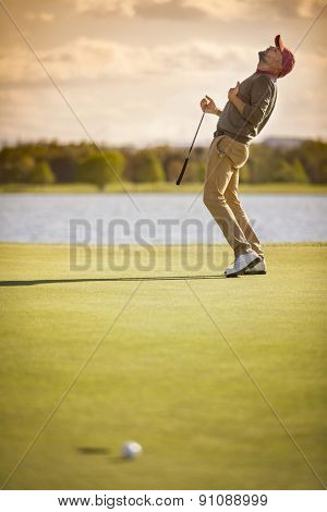 Male golf player showing emotion after ball missing hole at sunset.