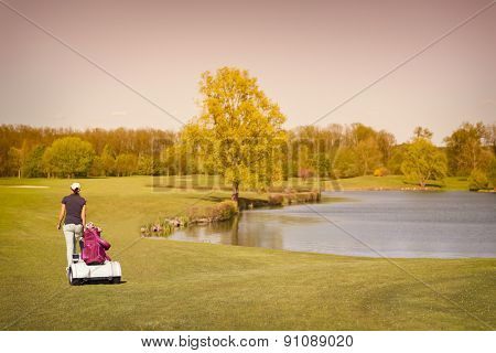 Woman golf player walking on fairway with lake at sunset.