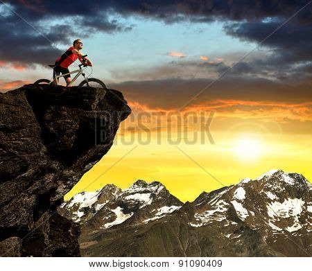 Cyclist on bike at sunset .In the background  Pennine Alps, Switzerland.