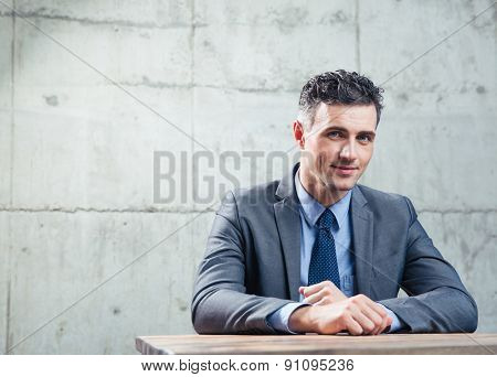 Happy businessman sitting at the table and looking at camera over concrete wall