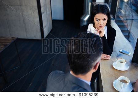 Businesswoman and businessman having coffee break and discussion in cafe