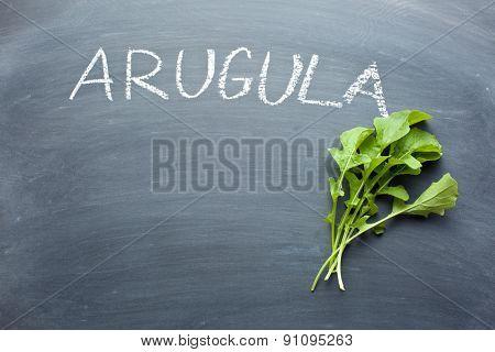 fresh arugula leaves on chalkboard