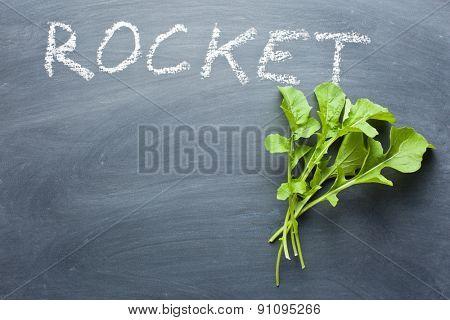 fresh rocket leaves on chalkboard