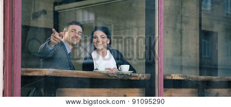 Happy businessman pointing on something in cafe