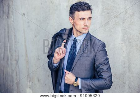Portrait of a thoughtful businessman holding jacket on shoulder and looking away