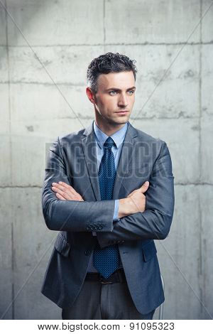 Portrait of a thoughtful businessman standing with arms folded over concrete wall and looking away