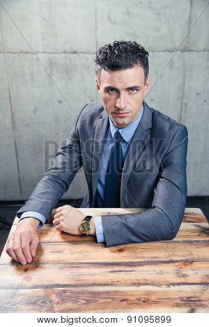 Confident businessman sitting at the table and looking at camera