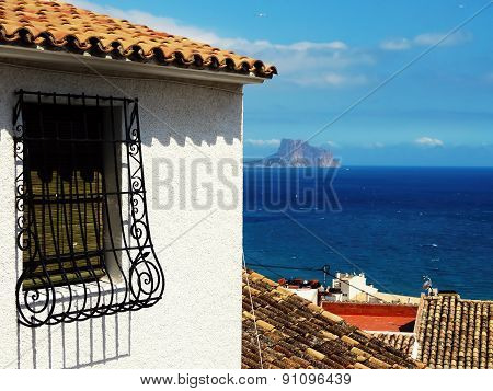Spanish grated window of old house and sea in background