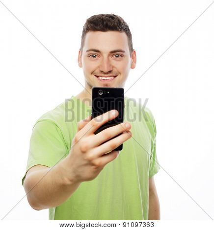 Life style, tehnology and people concept: a young man in shirt holding mobile phone and making photo of himself while standing against white background.