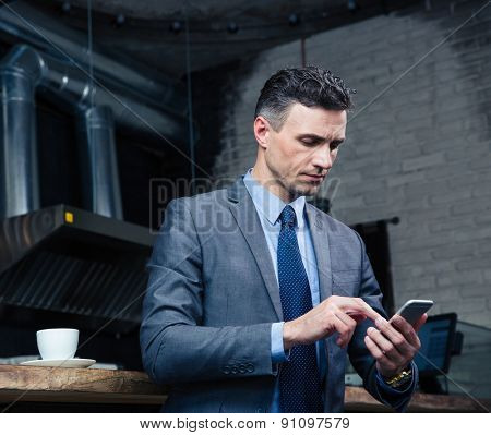 Serious handsome businessman using smartphone in cafe