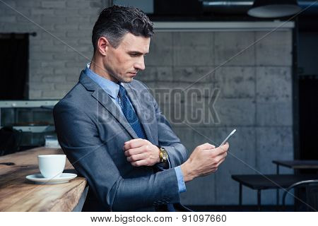 Confident businessman in suit using smartphone in cafe