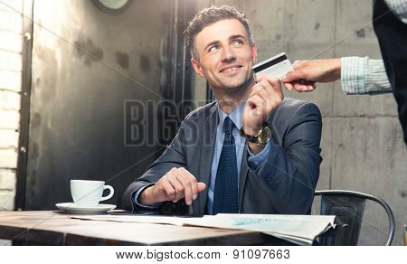 Handsome man giving bank card to waiter in cafe