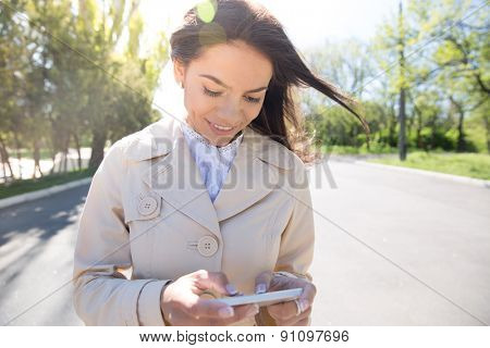 Smiling woman using smartphone outdoors