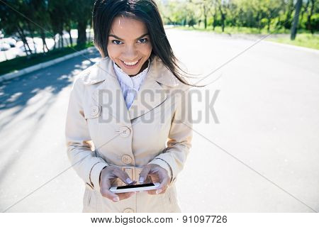Happy woman walking and using smartphone outdoors. Looking at camera