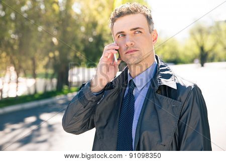 Pensive businessman in suit talking on the phone outdoors