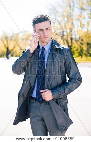 Handsome businessman in suit talking on the phone outdoors and looking away
