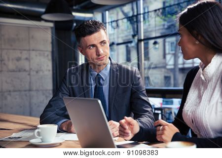 Handsome businessman and beautiful businesswoman using laptop together in cafe